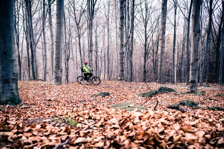 fitness motivation: Mountain biker on cycle trail in woods. Mountains in winter or autumn landscape forest. Man cycling MTB on rural country road. Sport fitness motivation and inspiration.