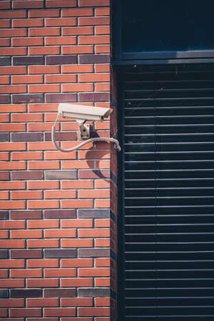 building safety: Security camera on office building, safety system. Surveillance camera looking and watching around, protection cctv device protect privacy or business property outdoors, urban city scene. Stock Photo