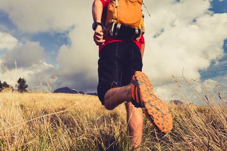 piernas hombre: Senderismo hombre, mochilero, escalador o corredor de pista en las monta�as en busca hermosa vista del paisaje inspirador. Fitness y estilo de vida saludable al aire libre en la naturaleza de verano. Foto de archivo