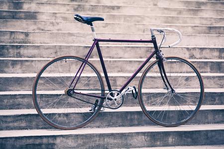clavados: bicicleta de carretera, bicicleta de piñón fijo en la calle de la ciudad hormigón. ciclismo urbano industrial, en bicicleta en las escaleras de la ciudad de cerca los pasos de la bicicleta, moto retro vendimia viejo, montar en bicicleta o los desplazamientos ecología. Concepto industrial.
