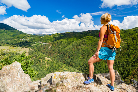 Hiking woman looking at inspirational mountains landscape. Fitness and healthy lifestyle outdoors in colorful summer nature. Trekking, camping and climbing travel concept. Stock Photo