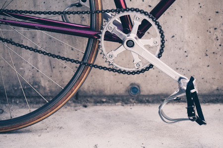 Road bicycle, fixed gear bike on city concrete street. Urban industrial cycling, bike chain on city scene bicycle closeup details, vintage old retro bike, cycling or ecology commuting. Industrial concept. 스톡 콘텐츠