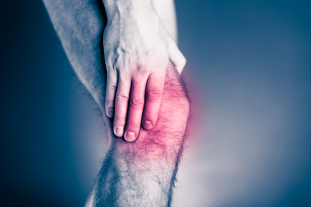 hand injury: Knee pain, physical injury. Male leg and muscle pain from running or training, sport physical injuries when working out. Man athlete holding leg with painful red spot over black and white background.