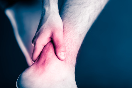 痛みが足と足首、物理的な損傷の痛みに足を。病気や事故、ランニングやトレーニング、スポーツの物理的な損傷操作するときの男性の脚や筋肉の