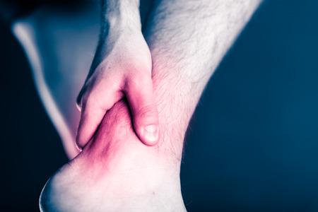 Bolesne nogi i kostki, po kolana w bólu, uraz fizyczny. Mężczyzna nogi i ból mięśni od choroby lub wypadku, prowadzenie lub szkolenia, sport, urazy fizyczne podczas pracy na zewnątrz. Mężczyzna sportowiec gospodarstwa nogę z bolesnym czerwona plama na czarnym i białym tle. Zdjęcie Seryjne