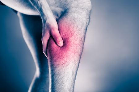 Calf pain, physical injury. Male leg and muscle pain from running or training, sport physical injuries when working out. Man athlete holding leg with painful red spot over black and white background.