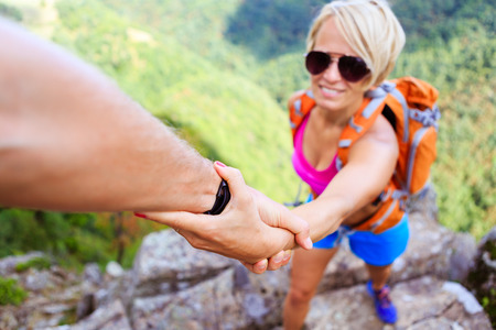 hiking: Helping hand couple, hiking help each other. Man and woman teamwork climbing or hiking with motivation and inspiration, beautiful inspirational landscape. Team sports and fitness. Selective focus on hands.