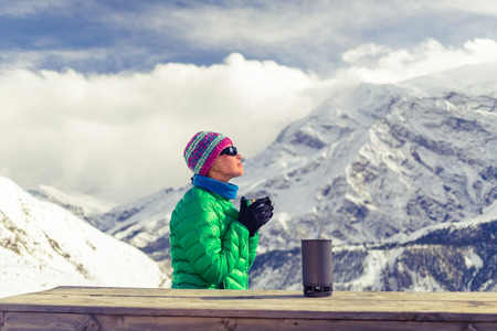 Young woman hiker camping, drink coffee or tea in beautiful Himalaya mountains on hiking trip. Inspirational landscape, Nepal. Active person resting outdoors in winter white nature.