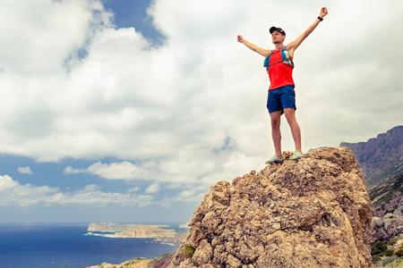 成功動機男して実行やハイキング、達成成功と幸福の概念、両手を上げ伸ばし登山やトレイル ランニング、屋外を健康な生活様式を祝う男