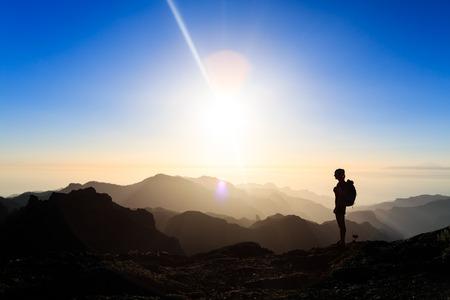iluminado a contraluz: Silueta de la mujer de senderismo en las montañas, puesta de sol y mar. Caminante femenino en la parte superior de la montaña en busca hermosa puesta de sol noche paisaje inspirado en Gran Canaria, Islas Canarias. Foto de archivo
