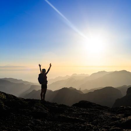 escalando: Mujer senderismo �xito silueta escalada en las monta�as, la motivaci�n y la inspiraci�n en hermosa puesta de sol y mar. Caminante femenino con los brazos arriba extendidos en cima de la monta�a mirando noche hermosa puesta de sol paisaje inspirador.