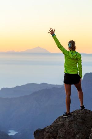 Vrouw succesvolle wandelen klimmen in de bergen, motivatie en inspiratie in de prachtige zonsondergang en de oceaan. Vrouwelijke wandelaar met wapens uitgestrekt op de berg boven kijken naar mooie nacht zonsondergang inspirerende landschap. Stockfoto