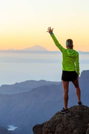 Woman successful hiking climbing in mountains, motivation and inspiration in beautiful sunset and ocean. Female hiker with arms up outstretched on mountain top looking at beautiful night sunset inspirational landscape.