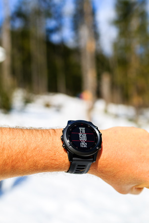 healthy looking: Runner on mountain trail looking at stopwatch smartwatch, activity tracker monitor, checking performance or heart rate pulse and training inspiring motivation. Healthy lifestyle, sport and fitness outdoors in nature.