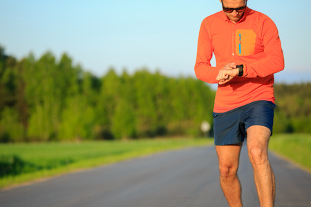 accomplish: Runner training and checking stopwatch smart watch, cross country running checking performance activity monitor tracker, GPS position or heart rate pulse. Sport smartwatch, inspiration and accomplish motivation.