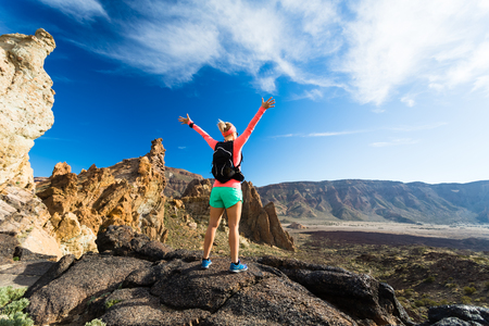 Caminante de la mujer con los brazos extendidos en las montañas. corredor femenino de la belleza, las manos en alto y disfrutar del paisaje inspirado en la senda sendero rocoso en Tenerife, Islas Canarias