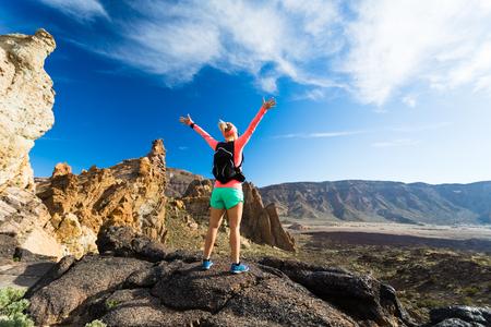 Wandelaar van de vrouw met uitgestrekte armen in de bergen. Beauty vrouwelijke agent, handen omhoog en geniet van inspirerende landschap op rotsachtig pad voetpad op Tenerife, Canarische Eilanden