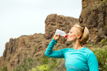 Trail runner woman cross country running and drinking water in mountains, inspirational landscape. Training and working out runner jogging and exercising outdoors in nature, rocky footpath on Canary Islands, Spain
