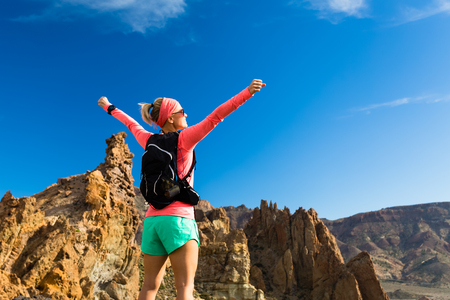 Woman hiker with arms outstretched in mountains. Beauty female runner, hands up and enjoy inspirational landscape on rocky trail footpath on Tenerife, Canary Islands