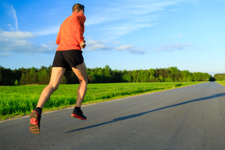 motivation: Man runner running on country road, training inspiration and motivation in summer sunset. Young athlete male training and doing workout outdoors in nature, sport and fitness lifestyle.