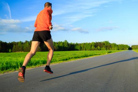 Man running bij de landweg, training inspiratie en motivatie in de zomer zonsondergang. Jonge atleet mannelijke opleiding en training buiten in de natuur, sport en fitness lifestyle.