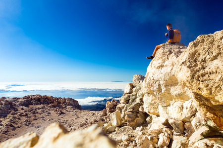 adventure: Man tourist hiker or trail runner looking at beautiful inspirational landscape in high mountains. Male runner with backpack, happiness freedom and enjoying inspiring view on rocky trail top of Teide mountain, Tenerife Canary Islands.