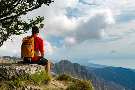 Man tourist hiker or trail runner looking at beautiful inspirational landscape in high mountains. Male runner with backpack, happiness freedom and enjoying inspiring view on rocky trail top of mountain, Italy.