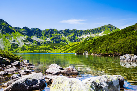 pond: Inspiring Tatra Mountains Landscape View, sunny day in summer Tatras. Looking at clear pond in green valley from mountain ridge over blue sunny sky, Poland in Europe Stock Photo
