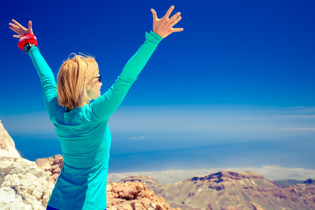 感動の山の風景と美しい景色と海の登山ハイキング成功した女性。女性ハイカーを両手を広げて山の頂上。 写真素材