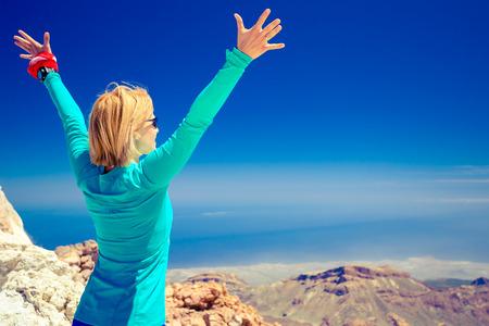 Frau erfolgreich Wandern Klettern in inspirierenden Berge, Landschaft, schöne Aussicht und das Meer. Weibliche Wanderer mit den Armen oben am Berg oben ausgestreckt.