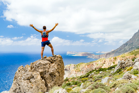 Success achievement running or hiking accomplishment or business concept, man celebrating with arms up raised outstretched trekking climbing trail running outdoors. Motivation and inspiration looking at beautiful landscape view. Stock Photo