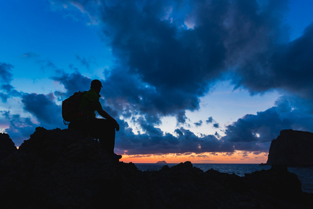 Hiker or runner silhouette backpacker, man looking at inspirational ocean landscape and islands on mountain peak. Accomplished man admire beautiful night and sea. Adventure and lifestyle concept. Stock Photo