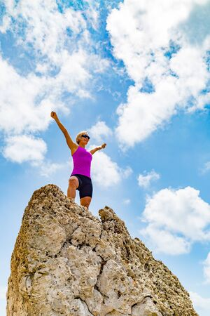 summits: Success achievement  running or hiking accomplishment business concept, woman celebrating with arms up raised. Hands outstretched on trekking or climbing trip. Trail Running concept outdoors in inspirational landscape. Stock Photo