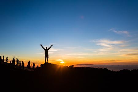 Man wandelaar silhouet met uitgestrekte armen in de bergen. Mannelijke agent of klimmer te kijken naar de zonsondergang. Business concept en de handen omhoog en geniet van inspirerende landschap, rotsachtig pad voetpad op Tenerife, Canarische Eilanden