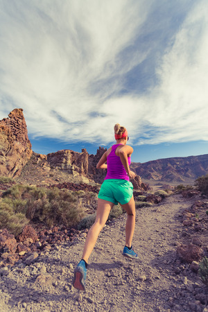 ultra: Woman trail running in mountains on dirt path. Beauty female runner jogging and training with backpack outdoors in nature, cross country running on rocky trail footpath on Tenerife with Teide mountain in background, Canary Islands. Stock Photo
