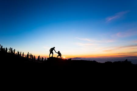 Para zespołowa Pomocna dłoń pomocy zaufania sylwetka w górach, zachód słońca. Zespół wspinaczy mężczyzny i kobiety pieszych, pomagać sobie nawzajem na szczycie góry, piękne inspirujący słońca krajobraz na Tenerife
