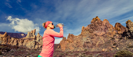 water  panoramic: Trail runner woman drinking water and running in mountains, inspirational landscape. Training and working out jogging and exercising outdoors in nature. Panoramic view on rocky footpath on Tenerife Canary Islands, Spain