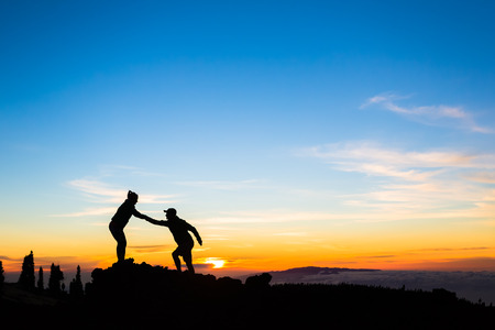 Teamwork couple helping hand trust help silhouette in mountains, sunset. Team of climbers man and woman hikers, help each other on top of mountain, climbing together, beautiful inspirational sunset landscape on Tenerife Canary Islands
