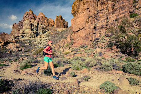 ultra: Young woman running in mountains on sunny summer day. Beauty female runner jogging and exercising outdoors in nature, trail running training on rocky trail footpath on Tenerife, Canary Islands Stock Photo