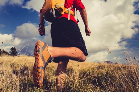 caminar: senderismo hombre o sendero corredor que recorre en paisaje de montaña de inspiración. Fitness y estilo de vida saludable caminante o excursionista a pie sobre la hierba seca, caen naturaleza del otoño. Viajar en Italia, Europa. Selectivo se centran en un zapato deportivo. Foto de archivo