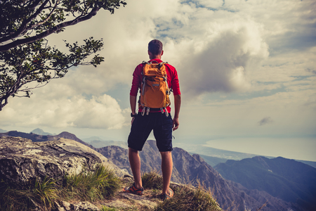 healthy looking: Hiking man, climber or trail runner in mountains, inspirational landscape view. Motivated hiker with backpack looking at beautiful view. Trekking, travel and tourism concept. Fitness and healthy lifestyle outdoors in summer nature.