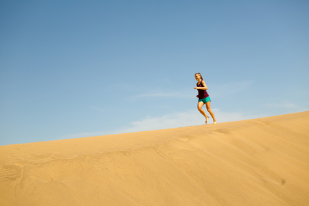power walking: Young woman running on beautiful inspirational desert dunes on sunny summer day. Female runner training and working out, jogging and exercising outdoors in nature, Gran Canaria, Canary Islands Spain. Stock Photo