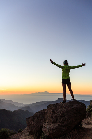 woman hands up: Woman successful hiking climbing silhouette in mountains, motivation and inspiration in beautiful sunset and ocean. Female hiker with arms up outstretched on mountain top looking at night sunset inspirational landscape. Stock Photo