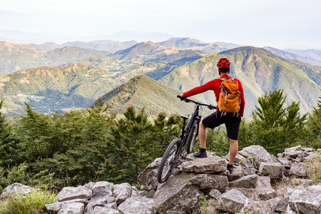 bike trail: Mountain biker looking at view on bike trail in autumn mountains. Rider cycling on rocky single track. Sport fitness motivation and  adventure inspiration.