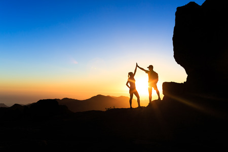 Teamwork couple helping hand trust help, silhouette success in mountains. Team of climbers man and woman. Hikers celebrate with hands up, help each other on top of mountain, climbing together, beautiful sunset landscape.
