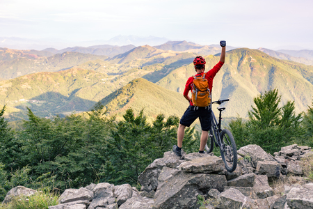 arms up: Mountain biker success, looking at view on bike trail in autumn mountains. Successful happy rider on rocks. Sport adventure motivation and inspiration.
