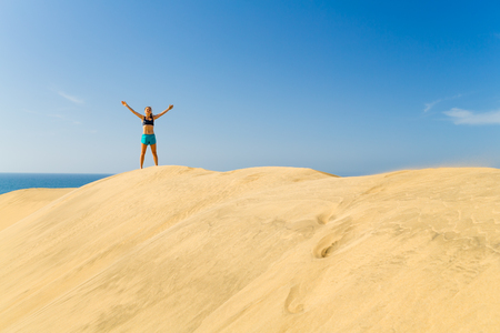 top mountain: Fitness successful happy woman with arms up outstretched celebrating on beautiful inspirational beach dunes on summer day. Beauty female runner training and exercising outdoors, business concept. Stock Photo
