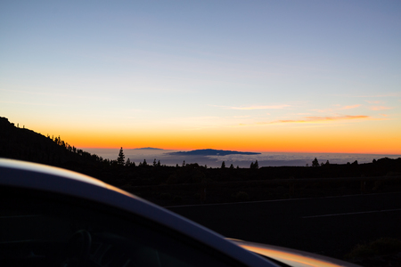 street night: Looking at inspirational landscape ocean view. Car driver or passenger on road trip looking at beautiful sunset sky on Tenerfie Canary Islands, Spain.