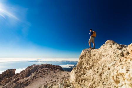 Toerist van de mens wandelaar of trail loper kijken naar mooie inspirerende landschap in het hooggebergte. Mannelijke agent met rugzak, geluk en genieten van inspirerende kijk op rotsachtige top van de berg, Spanje. Stockfoto