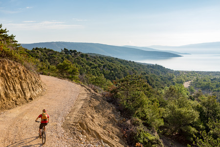 Mountain biker riding on bike at the sea and summer mountains. Man rider cycling MTB on dirt country road or single track. Sport fitness motivation, inspiration in beautiful inspirational landscape.